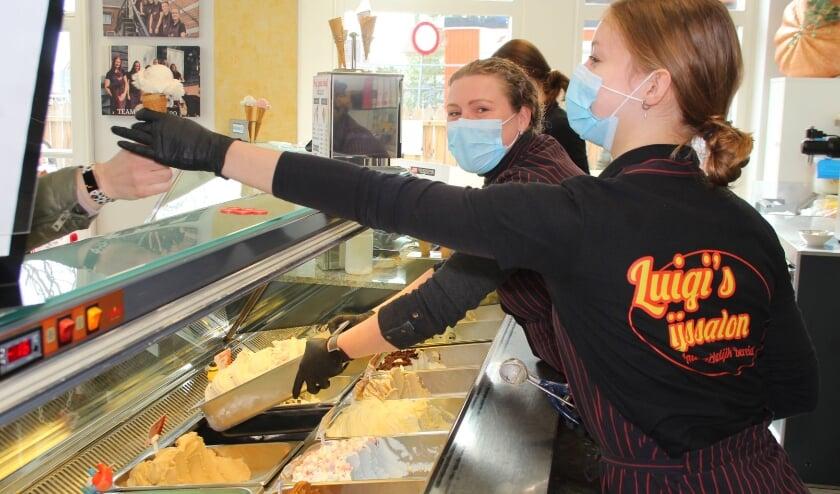 <p>Astrid van Dijken vult de bakken in de vitrine bij met het door Chris en haar ambachtelijk gemaakte ijs. Ondertussen helpen haar medewerkers de klanten die buiten op hun beurt wachten.</p>