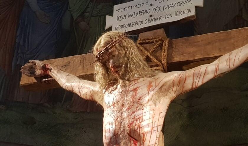 <p>Achterin de kerk van De Heuvel staat een tamelijk gruwelijk-realistisch beeld van de gekruisigde Jezus.</p>