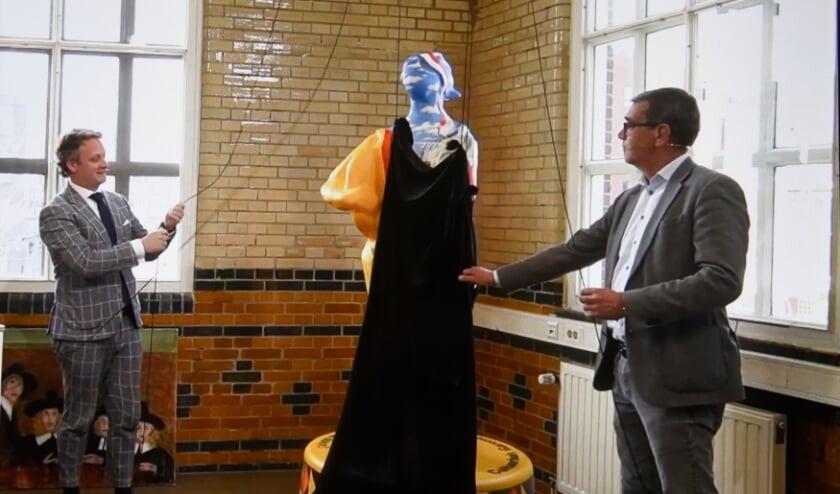 <p>Burgemeester Pieter Verhoeve en Gerard van Nieuwpoort onthullen het kaasmeisje dat als icoon voor Gouda 750 wordt beschouwd. Foto; Marianka Peters</p>
