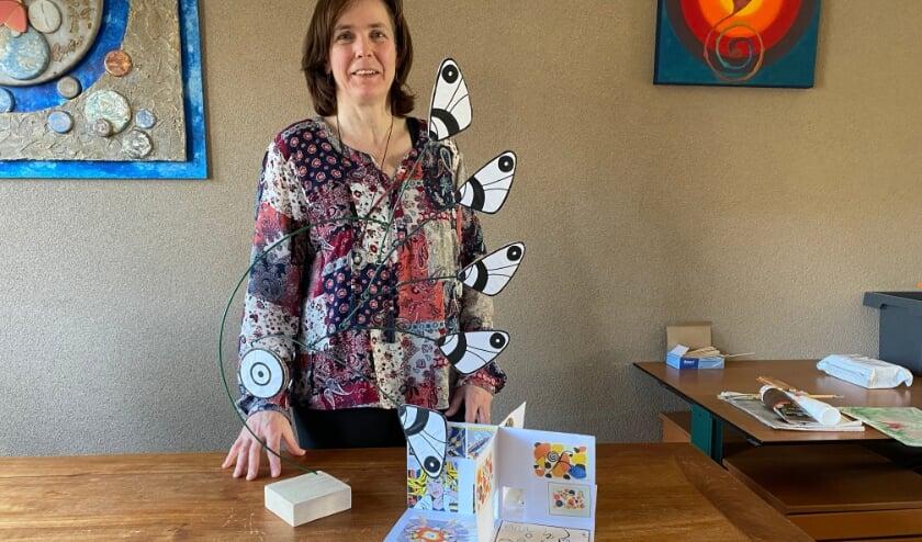 <p>Ineke van Geemen-Reuling bij het museum en de vlindermobile, projecten die ze kinderen op school laat maken. (foto: Karin van der Velden)</p>