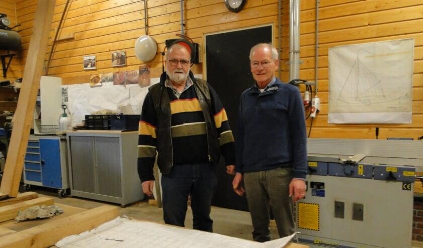 <p>Gerrit Vetten (links) en Tonnie Kerkhof bij een bouwtekening van de zomp in de werkplaats.</p>