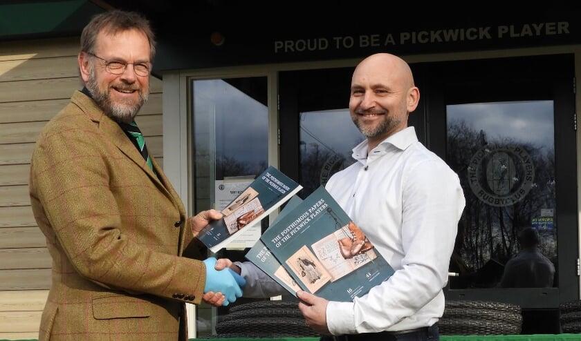 <p>Pickwicker Ruben Valstar overhandigt eerste exemplaar jubileumboek aan voorzitter van DRC The Pickwick Players, Kees Pricker</p>