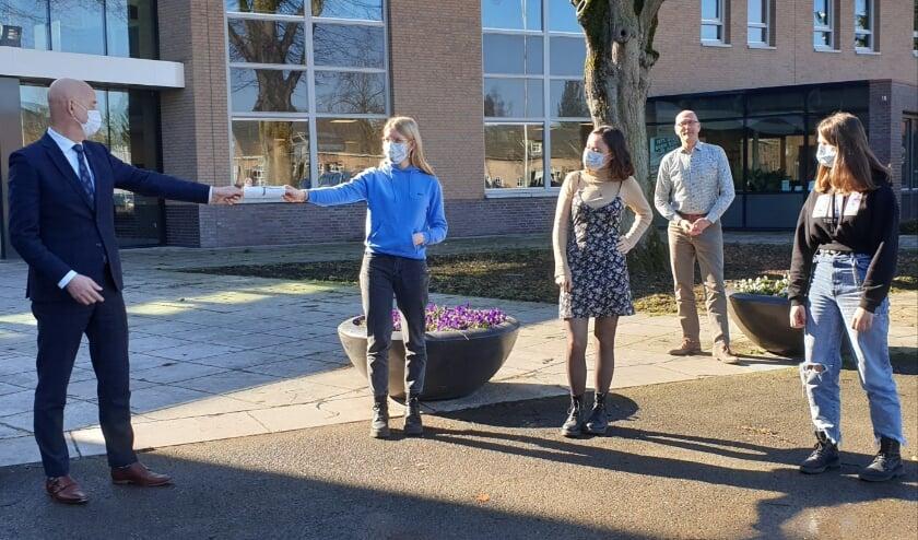 <p>De drie leerlingen overhandigen het klimaatmanifest aan burgemeester Wouters van de gemeente Eersel. Foto: Jeanne Versmissen-Adriaans&nbsp;</p>