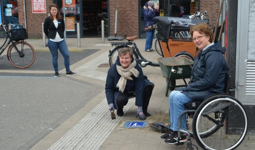 <p>Wethouder Brommersma (Wmo) en Danielle Janssen van werkgroep De Bilt voor Ieder(in) leggen in bijzijn van AH-manager Angela Gr&auml;ffner de eerste stoeptegel die op de geleidelijnen attendeert.</p>