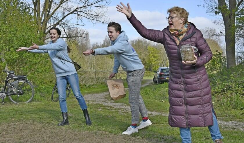 <p>Britte (vlnr) en Boaz van Die en wethouder Carla Koers zaaien met ferme slagen gifvrij bloemenmengsel&nbsp; in het Panovenpark (foto: Ab Hendriks).</p>