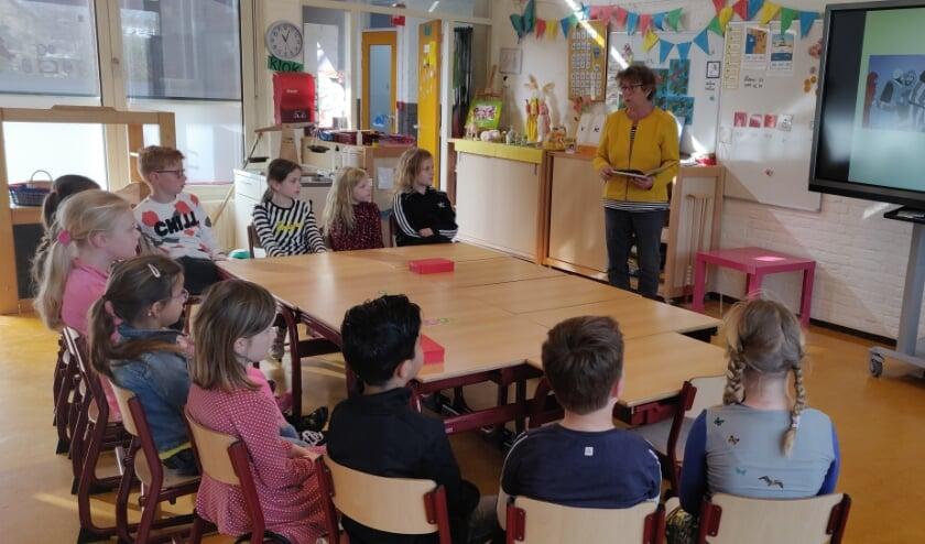 De kinderen uit groep 3/4 van de Lingelaar luisteren naar het paasverhaal
