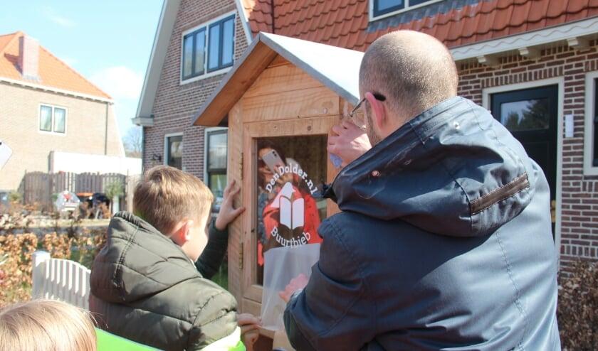 Paul van DenDolder.nl en Koen en Tim plakken de Buurtbieb-sticker op het deurtje.