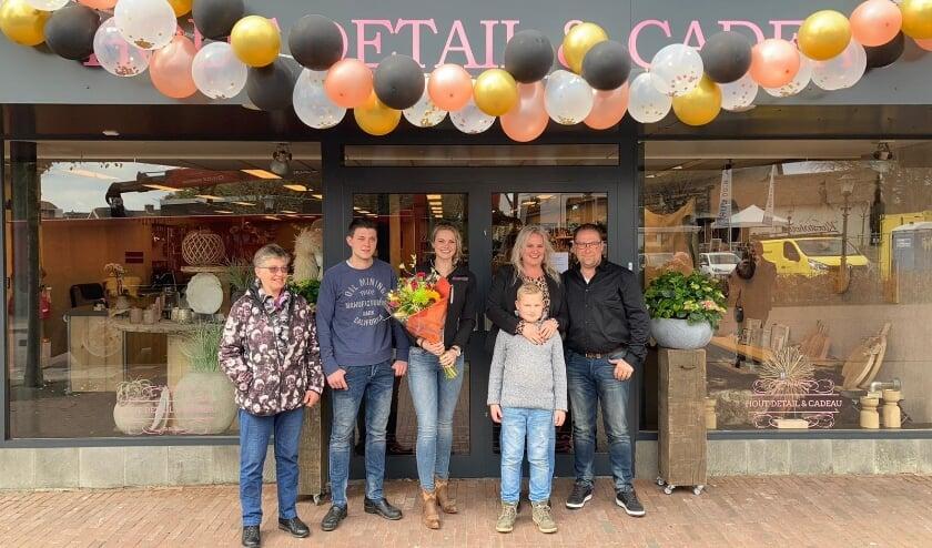 <p>Nathalie van Vliet met haar familie voor de geopende winkel Hout Detail & Cadeau.</p>
