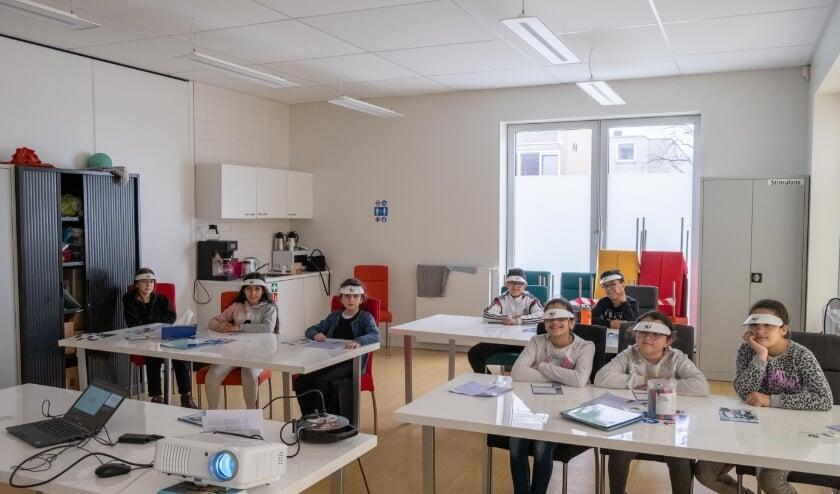 <p>Vrijwilligers van het WNF Regioteam Utrecht geven een gastles bij Petje Af in Kanaleneiland. Foto: Rudy van Miltenburg</p>