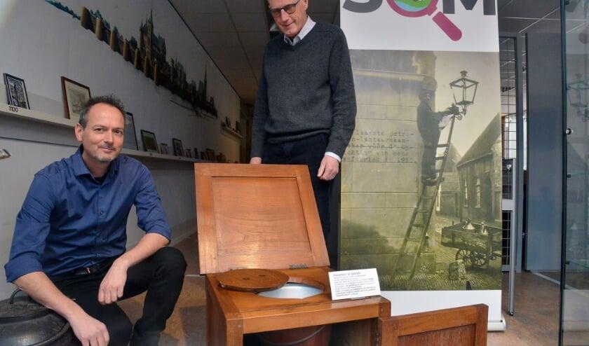 <p>Erik Vergeer en Lex van Wijk van het Stadsmuseum De Knoperij bij de oude poepdoos, de voorloper van het toilet. Foto: Paul van den Dungen</p>