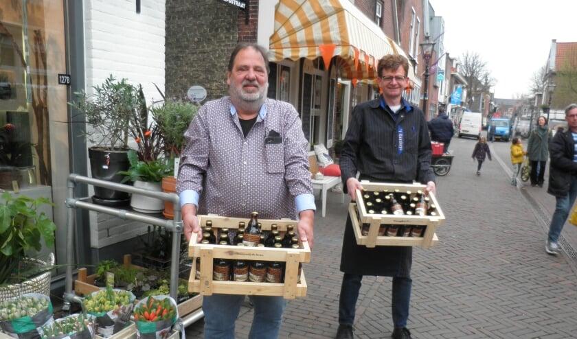 <p>Arnold Helders van de slijterij en Wim Fris van 't Kaashuys kunnen de kratten De Dorpsstraat bier nauwelijks aanslepen.</p>