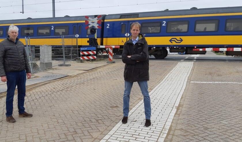 Wilbert van Bijlert en Jan van Ruijven voor de spoorwegovergang die na volgende week definitief wordt afgesloten.