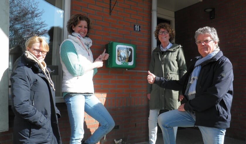 <p>Initiatiefnemers Wendy Grul en Hans Achterberg steken trots hun duim op samen met andere bewoners bij hun AED aan het Ebbehout.</p>