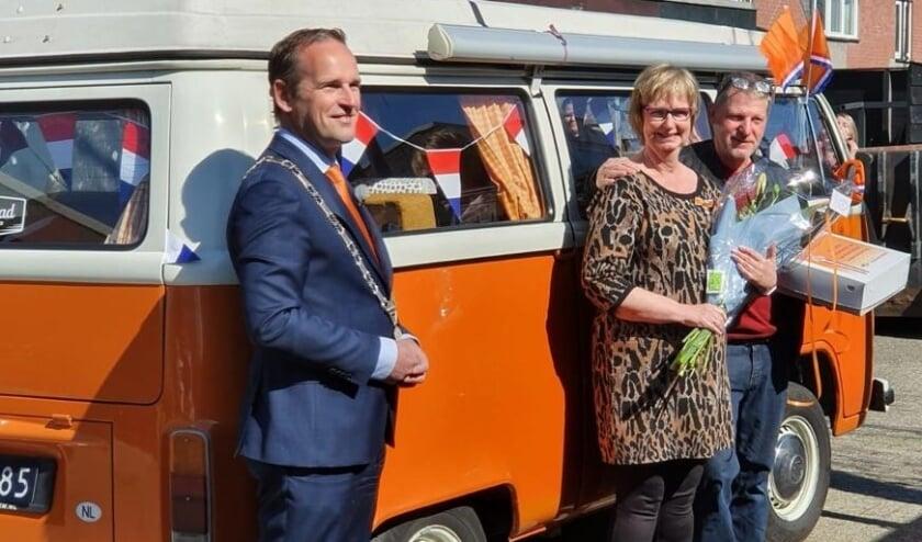 <p>Burgemeester van Hemmen poseert met de zojuist gedecoreerde Yvonne Bossche samen met haar partner voor het oranje busje dat de burgemeester maandag zelf bestuurde!</p>