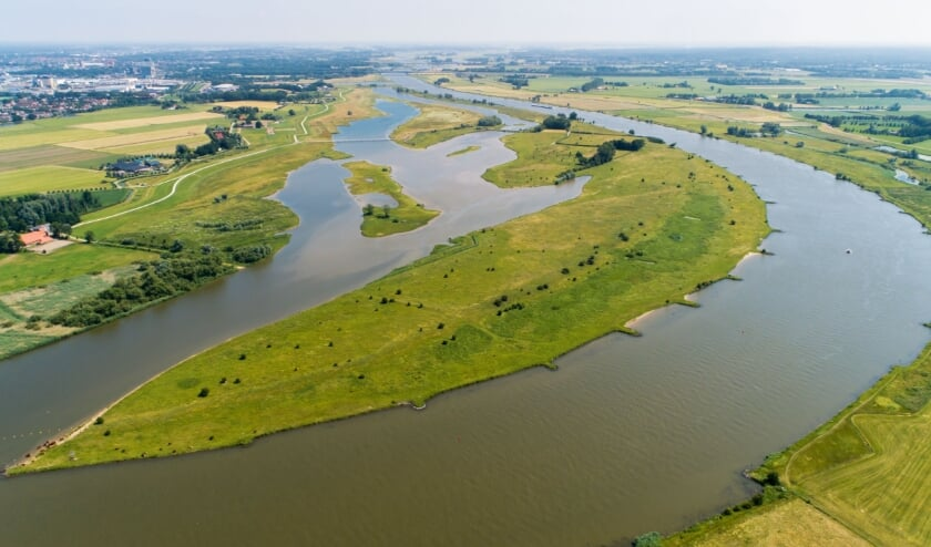 <p>Een foto uit het boek, gemaakt juni 2019. Aanblik in zuidelijke richting over de IJssel met op de voorgrond de Vreugendenrijkerwaard die noordelijk van Zwolle ligt. De winterdijk aan de Overijsselse zijde is recent landinwaarts gelegd. De hoofdgeul is van korte kribben voorzien. Aan de horizon rechts ligt de Veluwe. Links in de verte Zwolle, erachter Salland. </p>