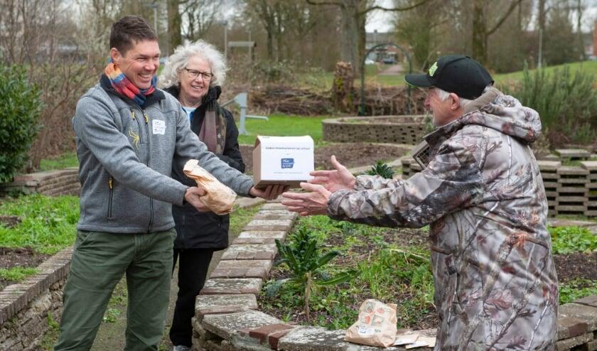 <p>Geert Koning van Natuurcentrum Arnhem overhandigt zaden aan vrijwilligers Reinda (links) en Cor (rechts) van Buurtmoestuin De Oosthof.</p>