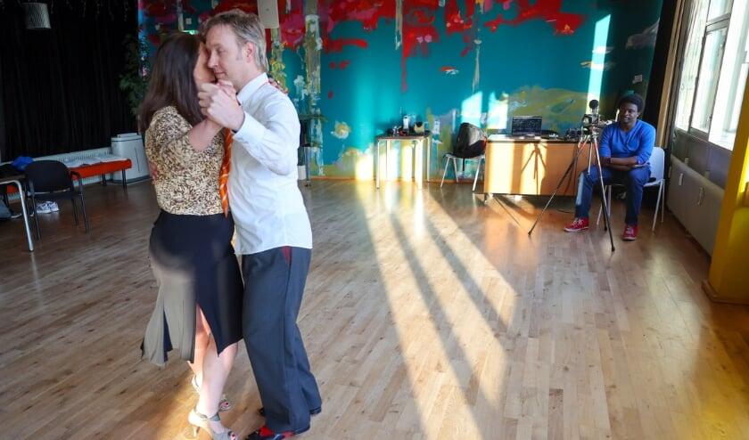 <p>Een dansend stel bij Tipo Tango in Eindhoven. Rechts: de filmende Francis Mbila. Hij schiet een video over de Argentijnse tango voor koningin M&aacute;xima. (Foto: Bert Jansen).</p>