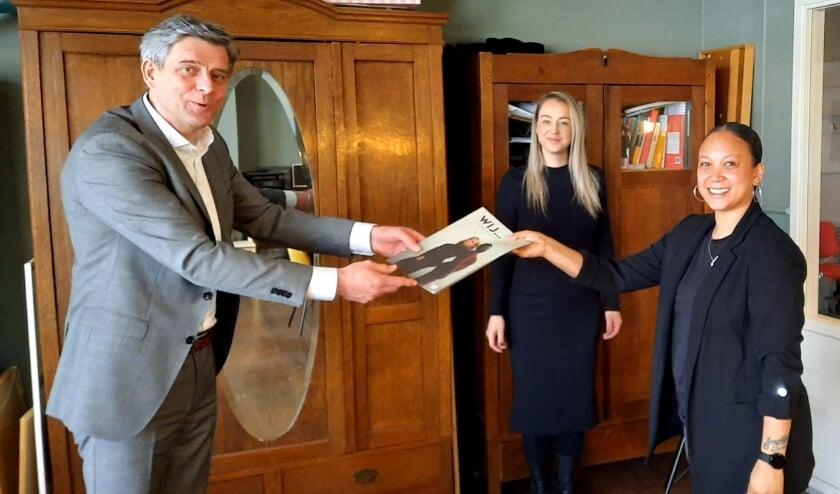 <p><em>Wethouder Roeland van der Zee overhandigt het magazine 'Wij… doorbreken de cirkel van geweld' aan Lovijah Veldt (meest rechts) en Sandra Rutjes (midden) van Stichting JAM (Foto: Gemeente Arnhem).</em></p>