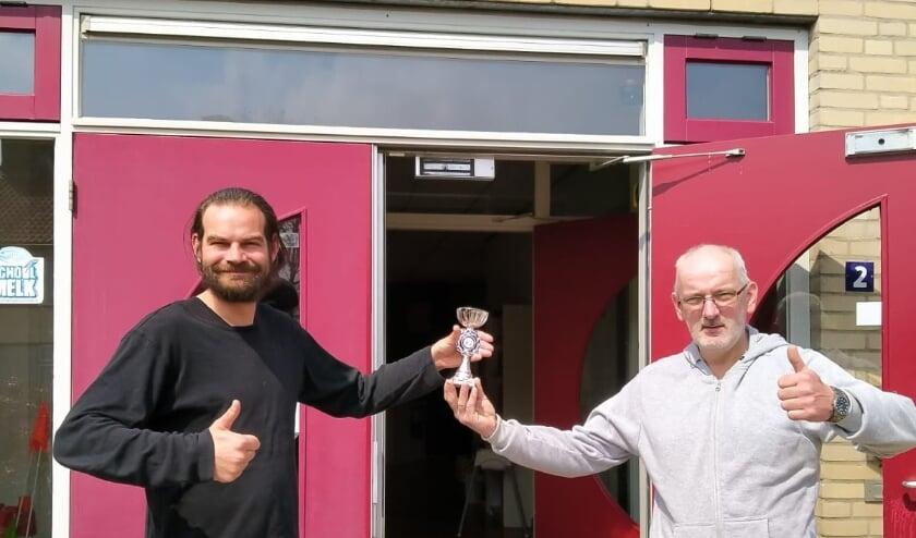 <p>Leerkracht Hans van Tussenbroek (links) neemt namen de leerlingen van basisschool Floriant de prijs van het Digitale Burgerweeshuis Jeugdschaaktoernooi 2021 in ontvangst van organisator Dirk van Zetten van Schaakvereniging RivierenlandScha</p>