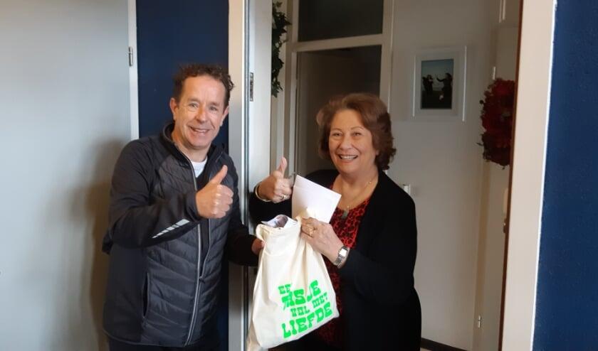 Namens Welzijn Rijswijk overhandigt verslaggever Frans Limbertie 'een tasje vol met liefde' aan mevrouw Wies Koppijn