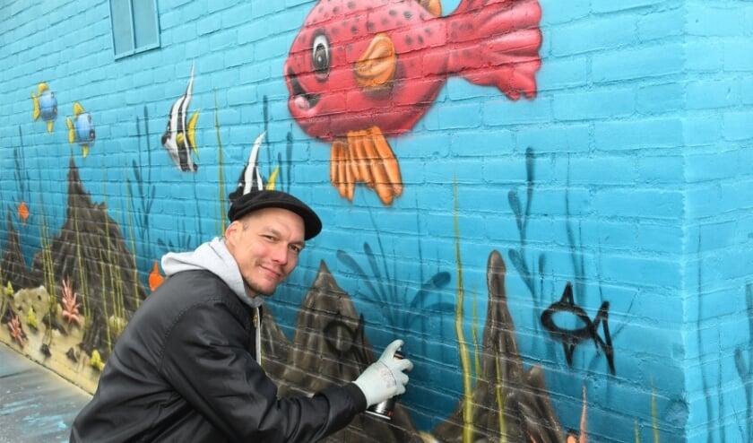 """<p><span cstyle=""""Fotocredit"""">Graffiti artist Finn Zweemer bij een van zijn kunstwerken. Foto: Marijke Vermeulen</span></p>"""