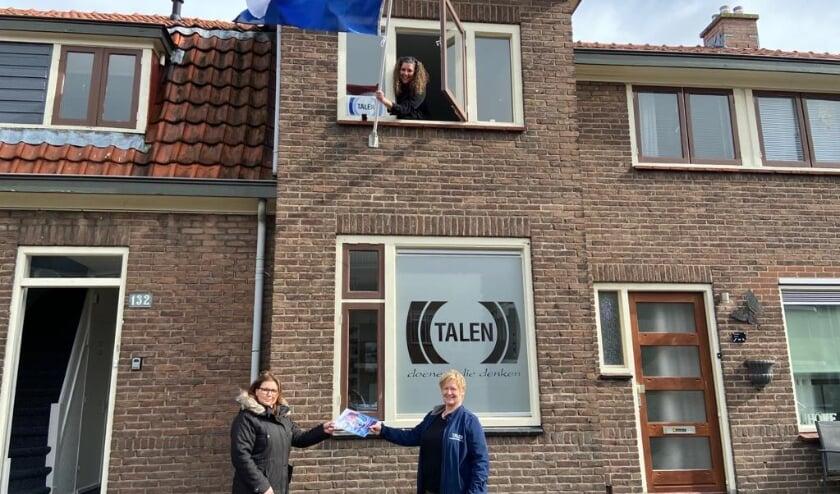 <p>Bij de kijk/opzichterswoning aan de Waterstraat 132 met de vlag Astrid Kuiken, bewonersbegeleider Portaal. Op straat neemt bewoonster mevrouw Benda (links) het renovatievoorstel in ontvangst van Conny Martens, bewonersbegeleider Talen.</p>