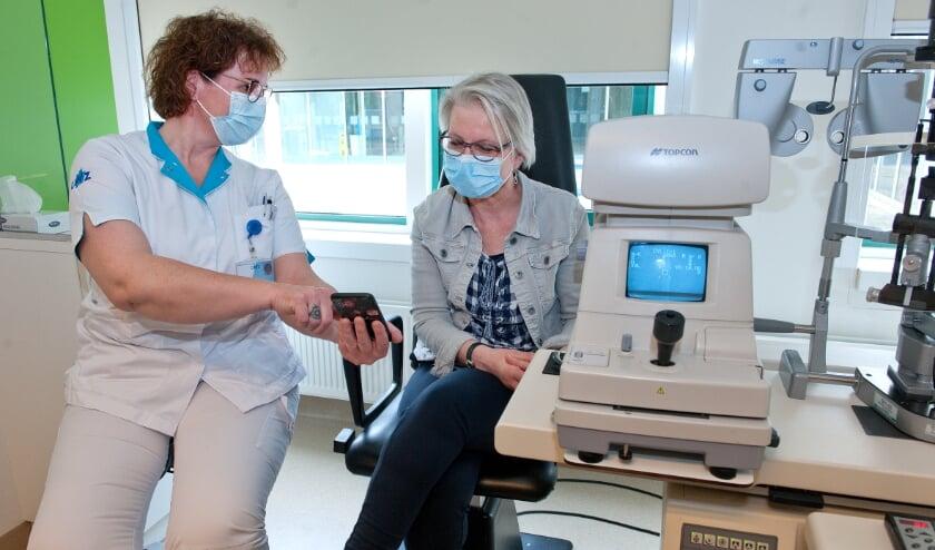 <p>Verpleegkundige en doktersassistent bij de oogkliniek Esther de Pee met een patiënt.&nbsp;</p>