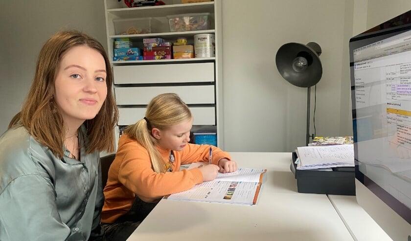 <p>Pabostudent Amber helpt leerling uit groep 5 thuis met schoolwerk.</p>