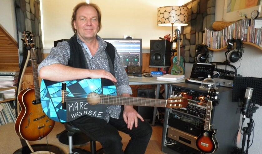 <p>Marc Lezwijn in zijn On Top Studio met zijn lievelingsinstrument de gitaar.</p>