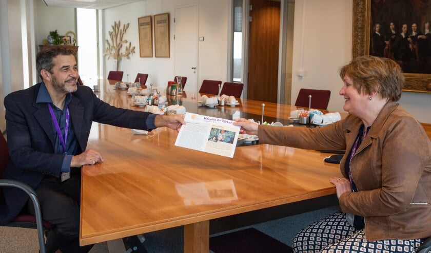 <p>Bestuurslid Heleen Roos van Hospice De Cirkel overhandigt de eerste jubileumjaarkrant aan ziekenhuisdirecteur Peter van der Meer.</p>