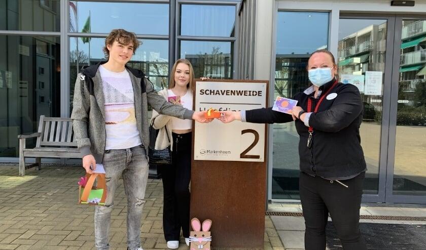 <p>Twee studenten overhandigen de attenties aan een medewerker van Schavenweide.</p>