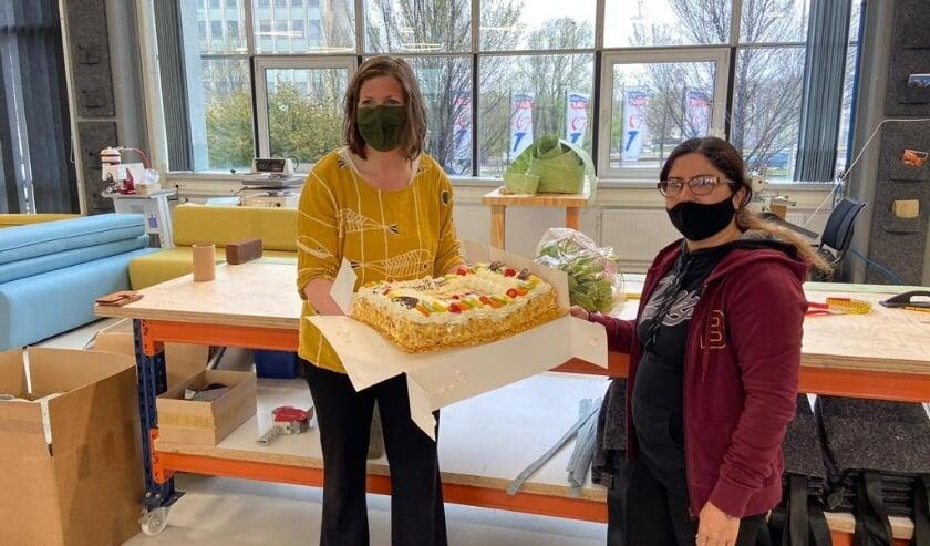<p>GroenLinks Raadslid Erlijn Wenink overhandigt taart aan i-did medewerker Shukria.</p>