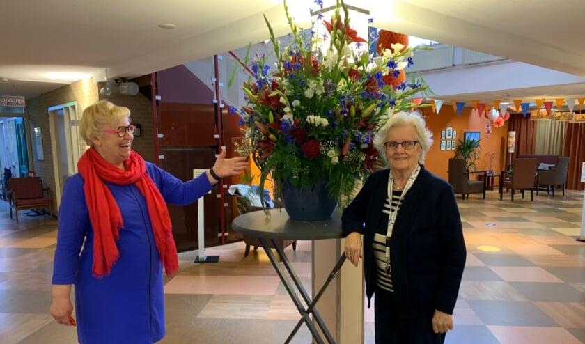 <p>Mevrouw van Velzen (r) was vol lof over het bloemstuk dat Jenny van Ark aan kwam bieden aan Brinkhoven.</p>