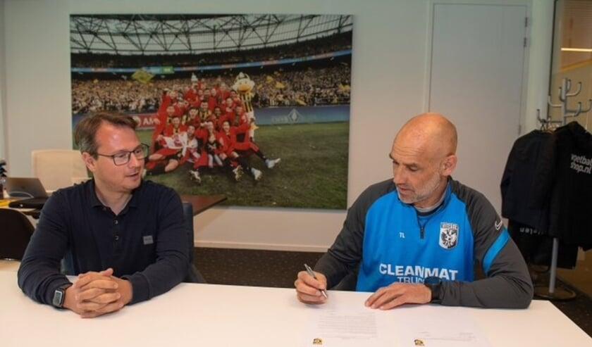 <p>Onder toeziend oog van technisch directeur van Vitesse, Johannes Spors, ondertekent hoofdtrainer Thomas Letsch zijn nieuwe, opengebroken, contract.</p>