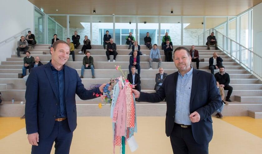 Wethouder Marcel Melissen overhandigt de sleutel van het nieuwe lyceumgebouw aan Toine Schinkel, bestuurder van het Lingecollege. Aan de sleutelhanger hangen wensen van lyceumleerlingen voor een mooie tijd in het nieuwe gebouw.