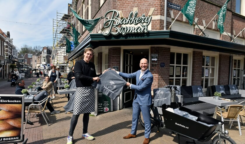 <p>Foto wethouder Van de Laar deelt fleecedekens uit op het terras van Bakkerij Bosman</p>