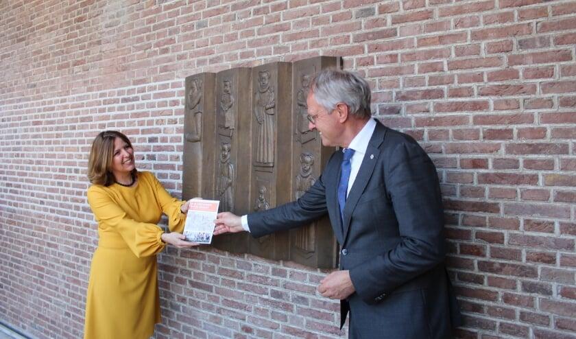 <p>Auteur Marjolijn Bergmann overhandigt in het Prinsenlogement de stadswandeling aan de commissaris van de Koning, Han Polman.</p>
