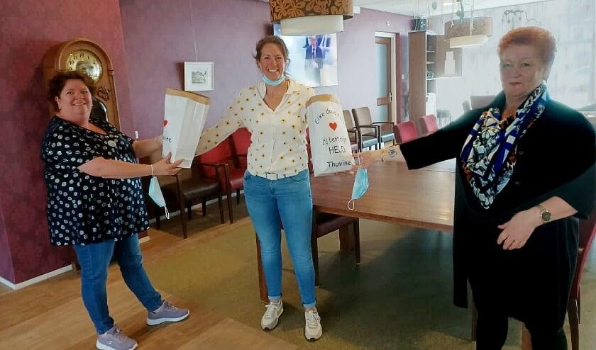 <p>Leonie Warris (midden) reikt 'Helden van de Zorg'-zakjes uit aan Helga Hartsteen (l) en Marian te Braak (r), zorggezellen van Thuvine.</p>