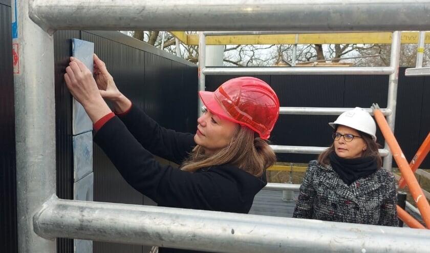 <p>Wethouder Cathelijne Bouwkamp plaatst de eerste tegel onder toeziend oog van directeur van Museum Arnhem, Saskia Bak.&nbsp;&nbsp;</p>