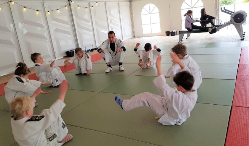<p>Endo Sjabbens verzorgt een judoles voor de jongste jeugd. Op de achtergrond wordt er &#39;gebootcampt&#39;.</p>
