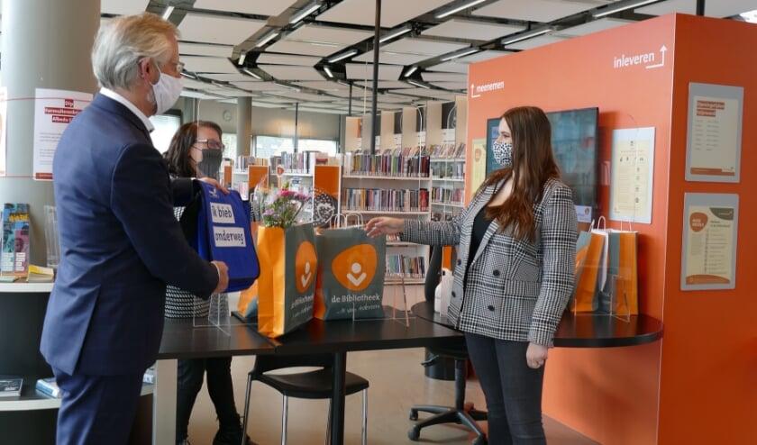 <p>Blij verrast neemt Amber Bijkerke de tienduizendste bestelling van de afhaalservice in ontvangst van Theo Kemperman, directeur Bibliotheek Rotterdam.</p>