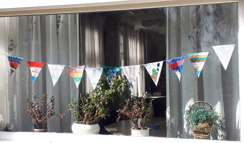 <p>Door kinderen gekleurde vlaggetjes voor de ramen van Inloophuis De Herberg aan de Dorpstraat 107 in Westervoort ter gelegenheid van Koningsdag.</p>
