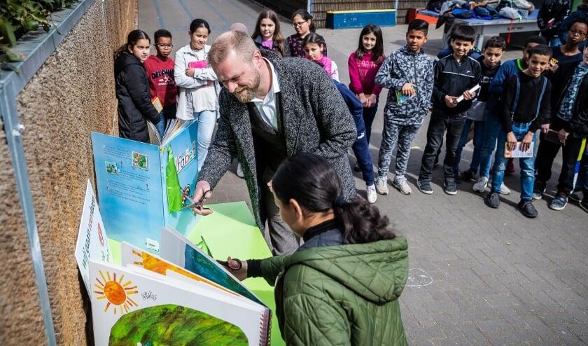 <p>Directeur Bert Hogemans opent de Bibliotheek op school samen met voorleeskampioen Aya.</p>