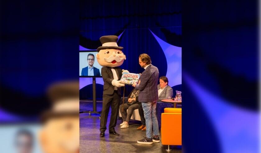 Vertrekkend wethouder Daan de Kort neemt het Veldhovens Monopoly in ontvangst.