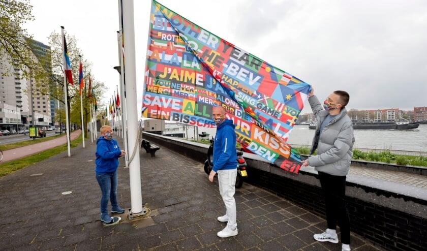 <p>Vrijwilligers Corry, Patrick en Tymen hijsen de vlag voor het Eurovisie Songfestival.</p>