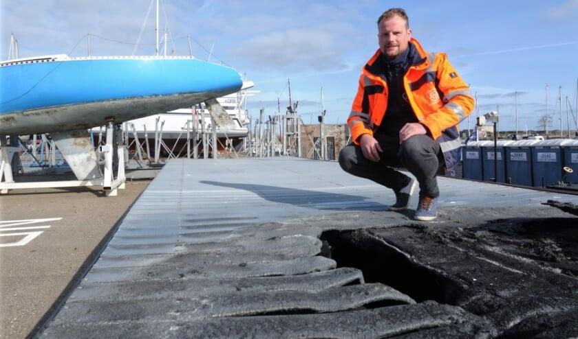 <p>Sven Heijboer op de vernielde steiger, met een gedumpt zeiljacht op de achtergrond.</p>