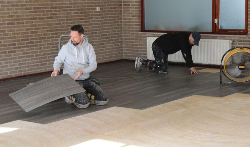 <p>Medewerkers van R.V. Vink uit Elst leggen een nieuwe vloer in het clubhuis van Oranje Wit. (Foto: Henk Jansen)</p>