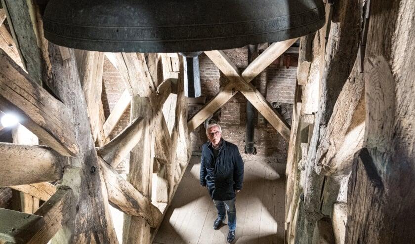 <p>Voorzitter Hans Vuuregge in het eeuwenoude klokkenstoel, onder de grote klok die een klein haarscheurtje heeft. Er wordt nu onderzocht hoe de klok gerepareerd gaat worden.</p>