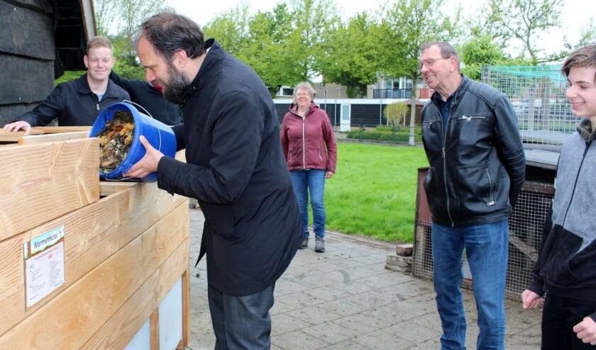 <p>Wethouder Erik van Zuylen heeft een openingshapje voor de tijgerwormen, onder toeziend oog van buurtbewoners.</p>
