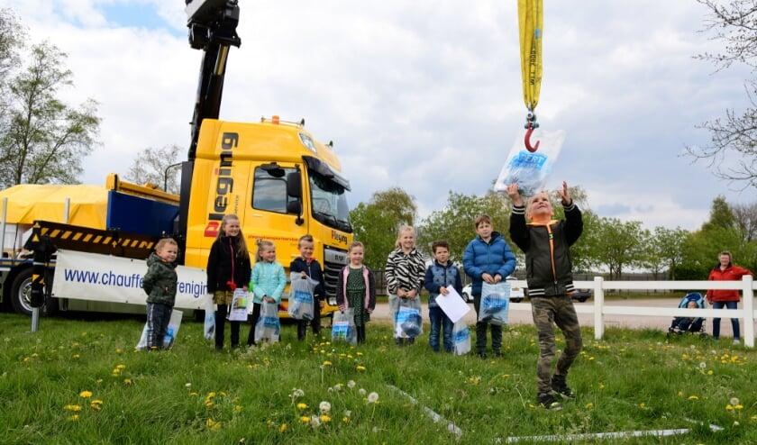 <p>Enthousiast ontvingen de negen jonge winnaars hun prijzen vanaf de kraanwagen. Op de foto: Evi, Sem, Nine, Vive, Jay, Stijn, Jessey, Merlin en Justin.&nbsp;</p>